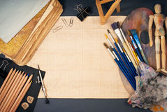 Ambience of art workplace. Multiple art tools and classic wooden dummy on a gray background Stock Photo