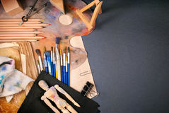 Ambience of art workplace. Multiple art tools and classic wooden dummy on a gray background Stock Image