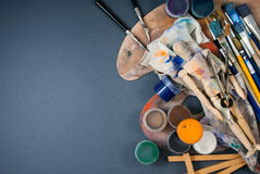 Ambience of art workplace. Multiple art tools and classic wooden dummy on a gray background Stock Photos