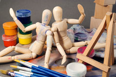 Ambience of art workplace. Two classic wooden dummies and multiple art tools Royalty Free Stock Image