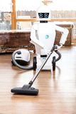 Ambient assisted living roboter is vacuuming. The floor of the living room stock photo