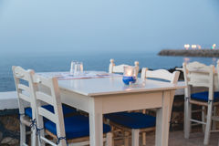 Ambient atmospheric evening on Greek coast, white tables in rest. Aurant Stock Photos
