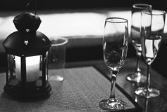 Ambient Drinking at Silver Wedding Party B&W. Silver Wedding Anniversary Party. An ambient lit candle lantern with different levels of champagne flutes. Black stock photos