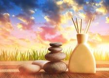 Ambientador de aire con los palillos del aroma y los guijarros de madera del zen en la puesta del sol Fotografía de archivo