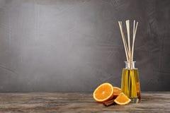 Ambientador de aire de l?mina arom?tico, rebanada de naranja y palillo de canela en la tabla de madera contra fondo gris foto de archivo libre de regalías