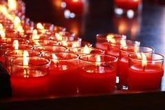 Ambiti di provenienza e strutture: il primo piano ha sparato di bruciatura delle candele rosse in vetro, tazza Fotografia Stock