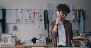 Ambitieuze manierontwerper die op mobiele telefoon in de documenten van de workshopholding spreken stock video