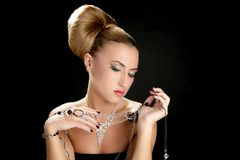 Ambition and greed in fashion woman with jewelry. In hands on black background stock images