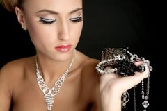Ambition and greed in fashion woman with jewelry. In hands on black background royalty free stock image