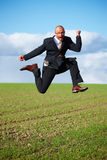 Ambitions - Businessman jumping in a field Stock Photo