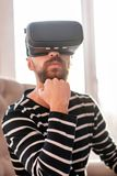 Ambitious bearded man estimating VR. Approaching progress. Low angle of concentrated appealing young man putting head on hand while wearing VR headset and Royalty Free Stock Image