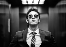 Ambitious. Black-and-white portrait of an ambitious business guy wearing sunglasses Royalty Free Stock Photography