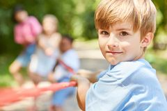 Ambitious boy in tug-of-war competition. Ambitious boy competing in tug-of-war with friends in the park Royalty Free Stock Photography