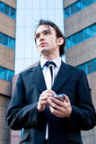 Ambitious business executive. A young handsome formally dressed businessman (business executive) is using his palmtop, background is a corporate building with stock photo