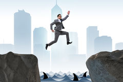 The ambitious businessman jumping over the cliff. Ambitious businessman jumping over the cliff Stock Photo
