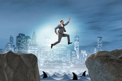 The ambitious businessman jumping over the cliff Stock Image