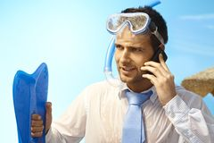 Ambitious businessman on summer holiday. Ambitious young businessman talking on mobilephone on summer holiday Stock Image