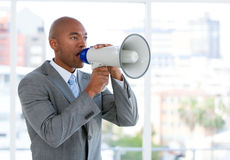 Ambitious businessman yelling through a megaphone. In the office stock photo