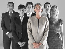 Ambitious businesswoman with team of professionals against gray background royalty free stock photos