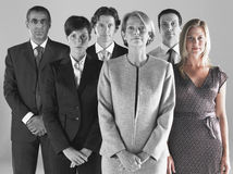 Ambitious businesswoman with team of professionals against gray background Royalty Free Stock Image