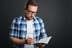 Ambitious careful man making some notes. Focused writer. Organized devoted calm guy compiling a schedule while using his journal and a pencil for writing it down Royalty Free Stock Images