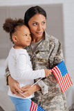 Ambitious caring mother celebrating the arrival. Strong together. Wonderful pretty charming ladies hugging after being apart for some time and holding flags in royalty free stock photos