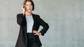 Ambitious corporate intern female copy space. Ambitious corporate intern. Young attractive female in glasses. Hand on hip. Copy space on grey background stock photos