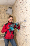 Ambitious craftswoman with caulking hammer in front of brick wal Stock Image