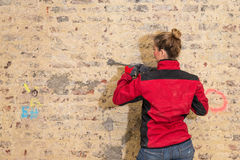 Ambitious craftswoman with caulking hammer in front of brick wal Stock Images