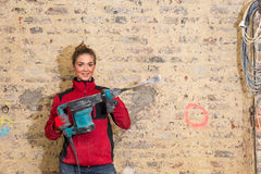 Ambitious craftswoman with caulking hammer in front of brick wal Stock Photography