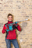 Ambitious craftswoman with caulking hammer in front of brick wal Stock Photos