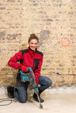Ambitious craftswoman with caulking hammer in front of brick wal Royalty Free Stock Photos