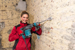 Ambitious craftswoman with caulking hammer in front of brick wal Royalty Free Stock Image