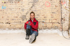 Ambitious craftswoman sitting on floor in front of brick wall in Stock Images