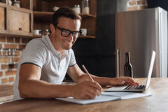 Ambitious creative man writing down his ideas. To do list. Handsome enthusiastic diligent guy working as a freelancer while developing personal project and Royalty Free Stock Photo