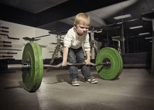 Ambitious, Determined little boy trying to lift Royalty Free Stock Photos