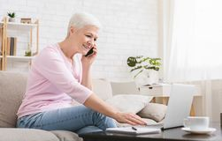 Ambitious elderly lady managing project from home. Freelance for any age. Ambitious elderly lady managing project from home, talking on phone and using laptop stock image