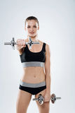 Ambitious girl exercising with dumbbells on a grey background Royalty Free Stock Images