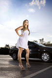 Ambitious girl. In a white dress near the black car Royalty Free Stock Photography