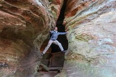 An ambitious hiker decides to climb in a huge crevice stock photo