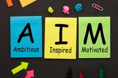 Ambitious Inspired Motivated AIM. Ambitious Inspired and Motivated AIM text on color notes and office supplies on black background. Motivational Acronyms royalty free stock photography
