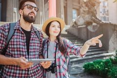 Ambitious and joyful young people stand outside and look forward. He holds tablet. She points forward. stock images