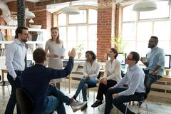 Male worker raise hand asking question at office teambuilding. Ambitious male employee raise hand ask question to female presenter at meeting, men show activity royalty free stock images
