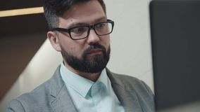 Ambitious man with glases and beard: he sits in front of the laptop