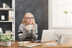 Business woman thinking about successful strategy. Ambitious pensive business woman having coffee and thinking about successful strategy, dreaming about Stock Image