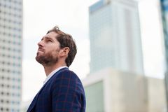 Ambitious young businessman with a vision standing in the city. Ambitious young businessman wearing a blazer looking at the office building landscape while Royalty Free Stock Photos