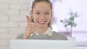 Ambitious Young Latin Woman doing Thumbs Up in Office