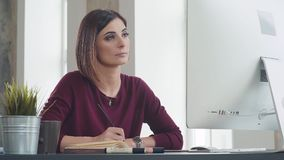 Ambitious young woman in the workplace looks at the monitor screen