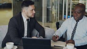 Ambitni biznesmeni dyskutuje początkowego projekt w nowożytnym szklistym lobby Amerykanina Afrykańskiego Pochodzenia przedsiębior zbiory wideo