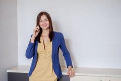Ambitny bizneswoman opowiada telefonem przy nowożytnym biurowym miejscem pracy obrazy royalty free